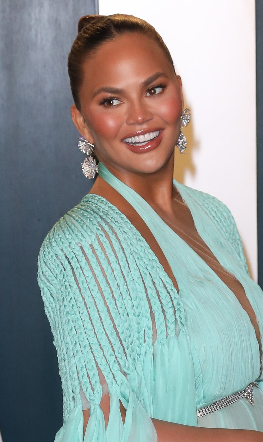 Chrissy Teigen smiling in a blue-maxi dress and large diamond earrings