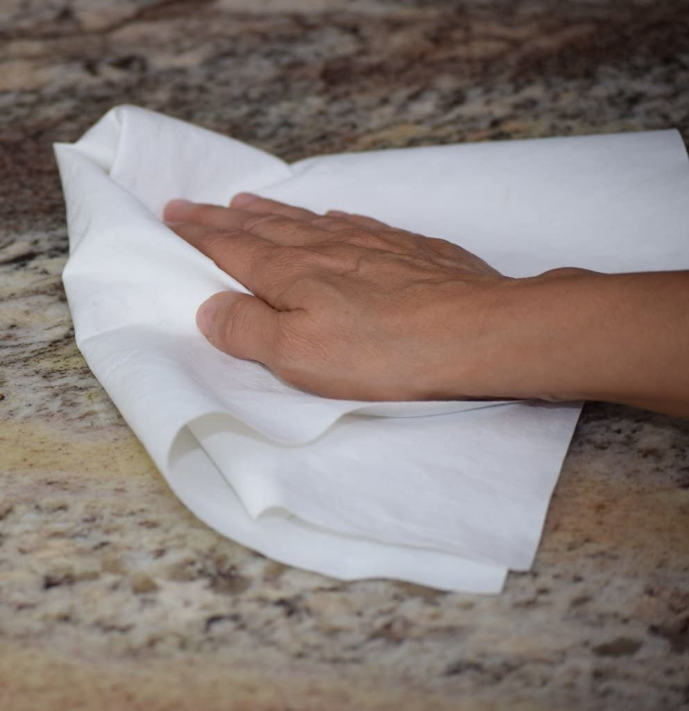person wiping their counter with the cloth
