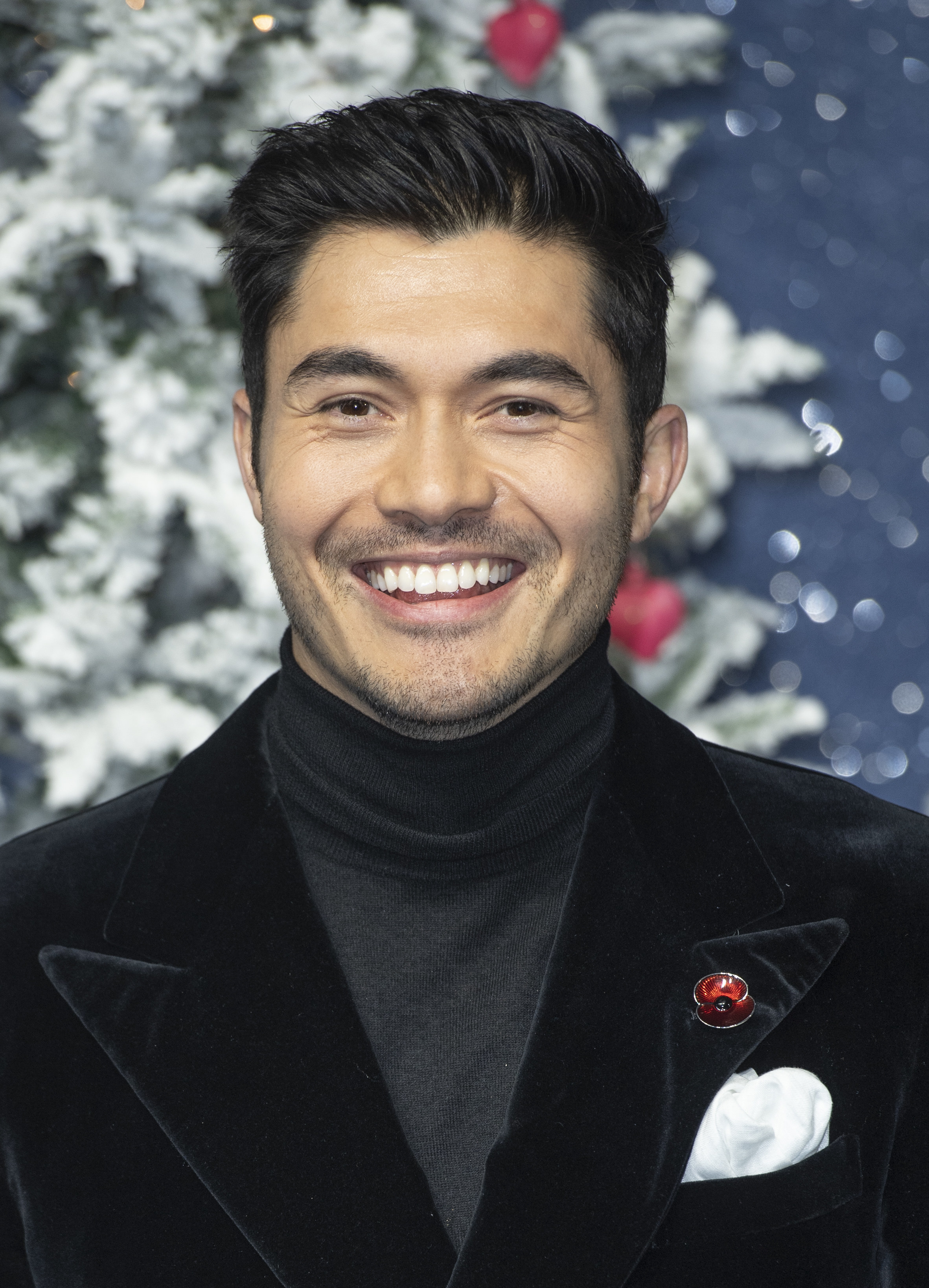 Henry Golding in a turtleneck and suit, smiling