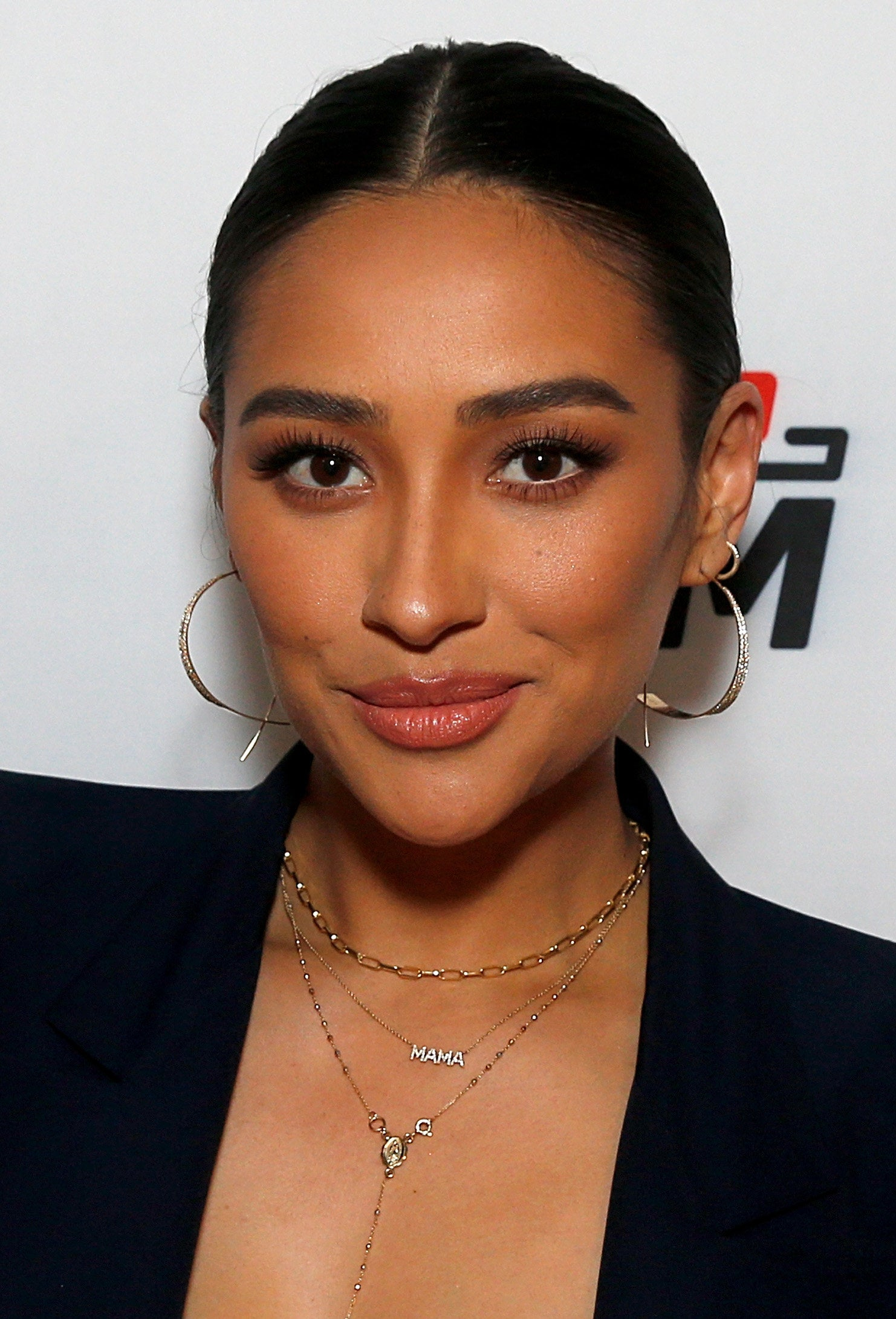 Shay Mitchell with her hair slicked back into a bun, wearing a blazer as she smiles at the camera