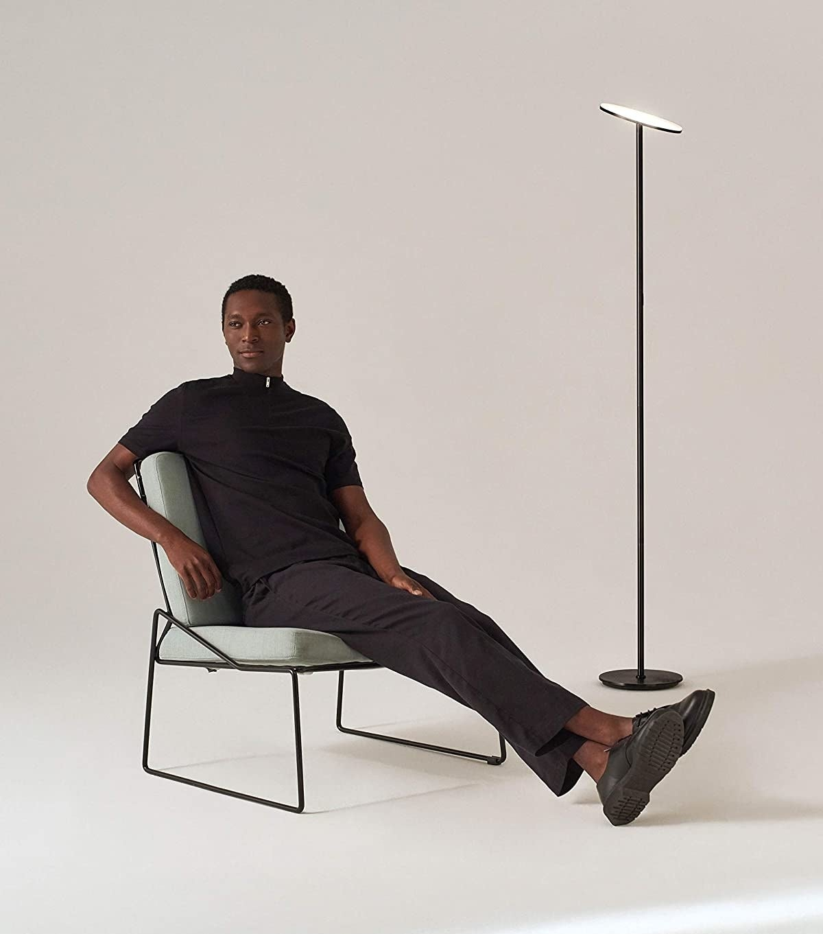 person sitting on chair next to standing lamp