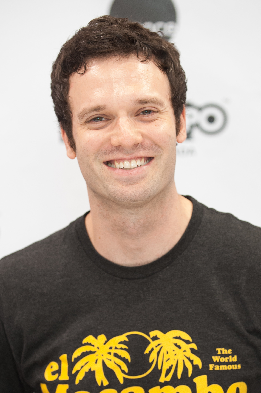 Jake Epstein posing in a black t-shirt