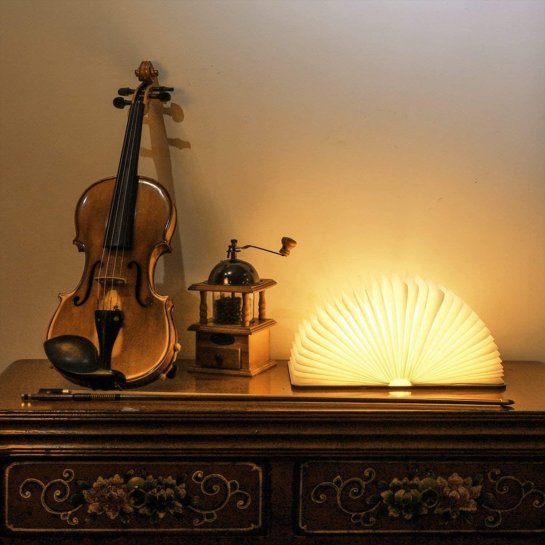 book light on a dresser next to a violin