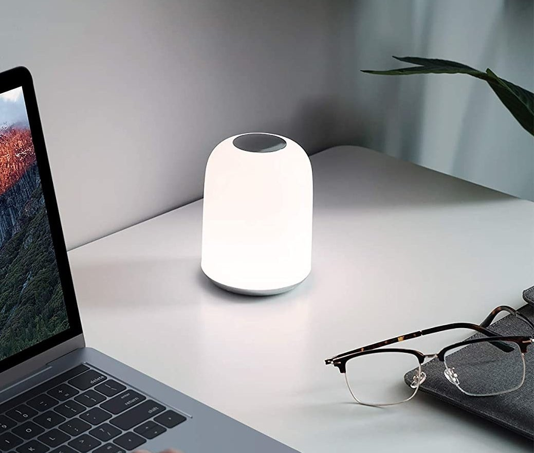 table lamp next to a laptop and glasses