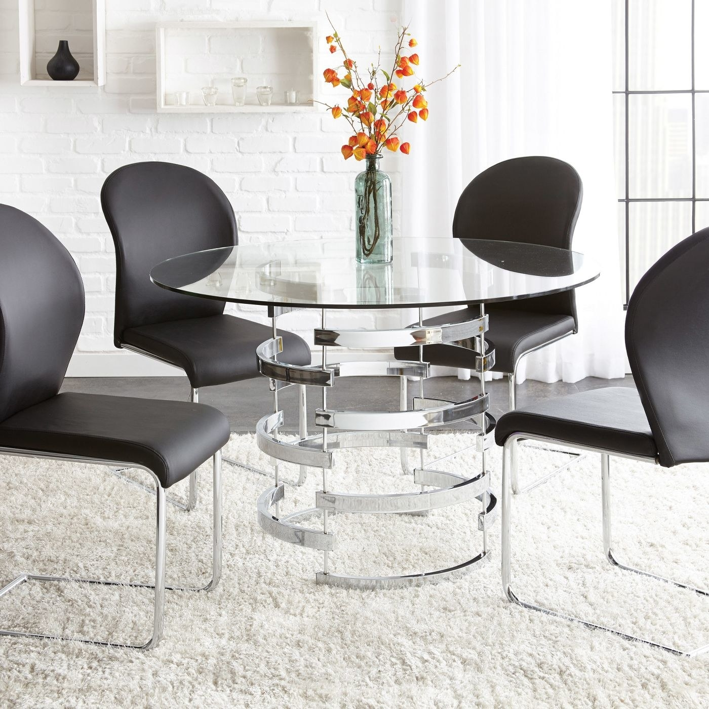 A chrome round dining table with a glass top