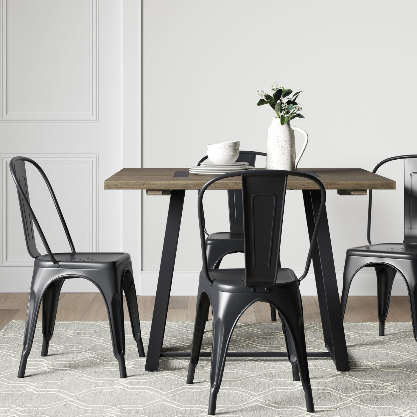 A brown drop leaf dining table with a black metal base