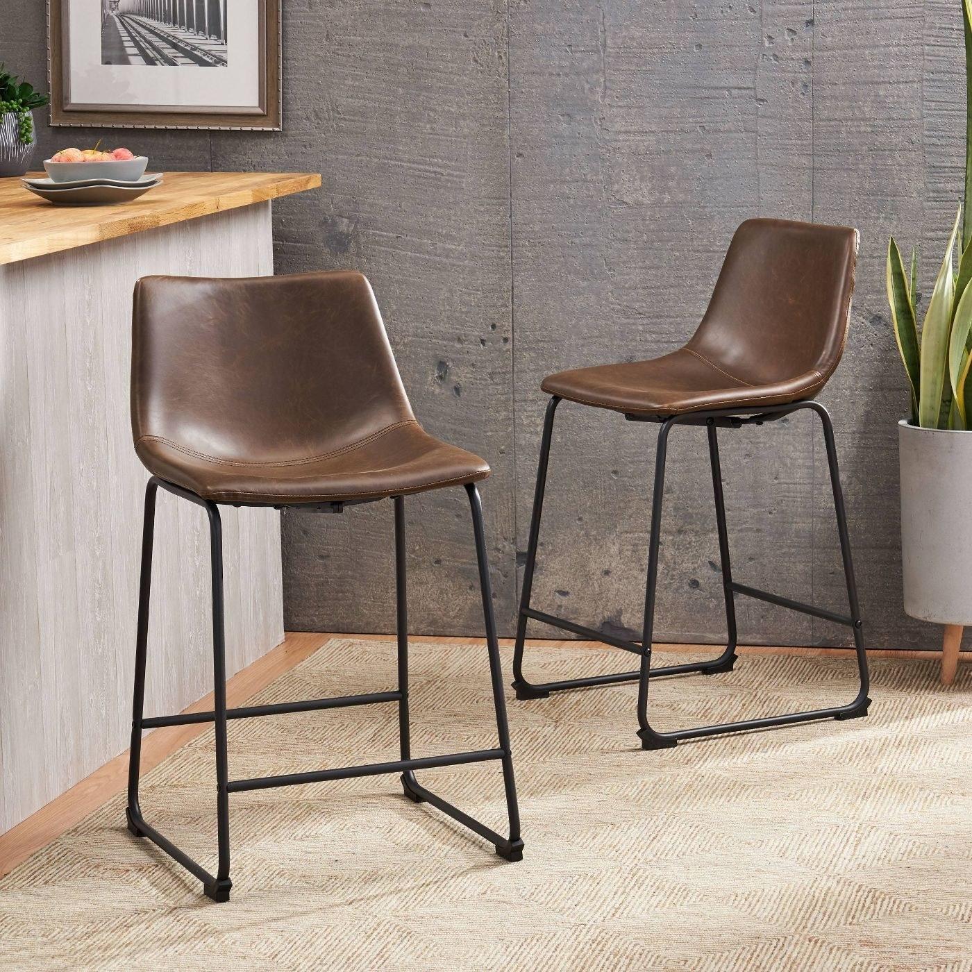 Two brown faux leather bar stools with black metal bases