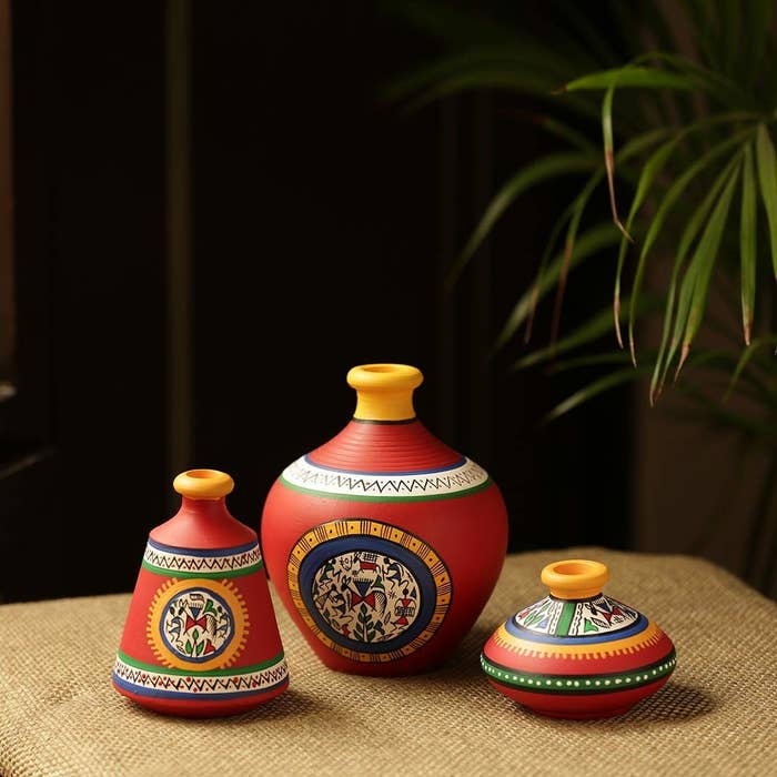 A set of red hand-painted Warli pots