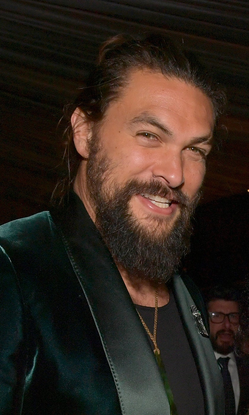 Jason Momoa smiling with his hair pulled back into a bun and a green, velvet suit