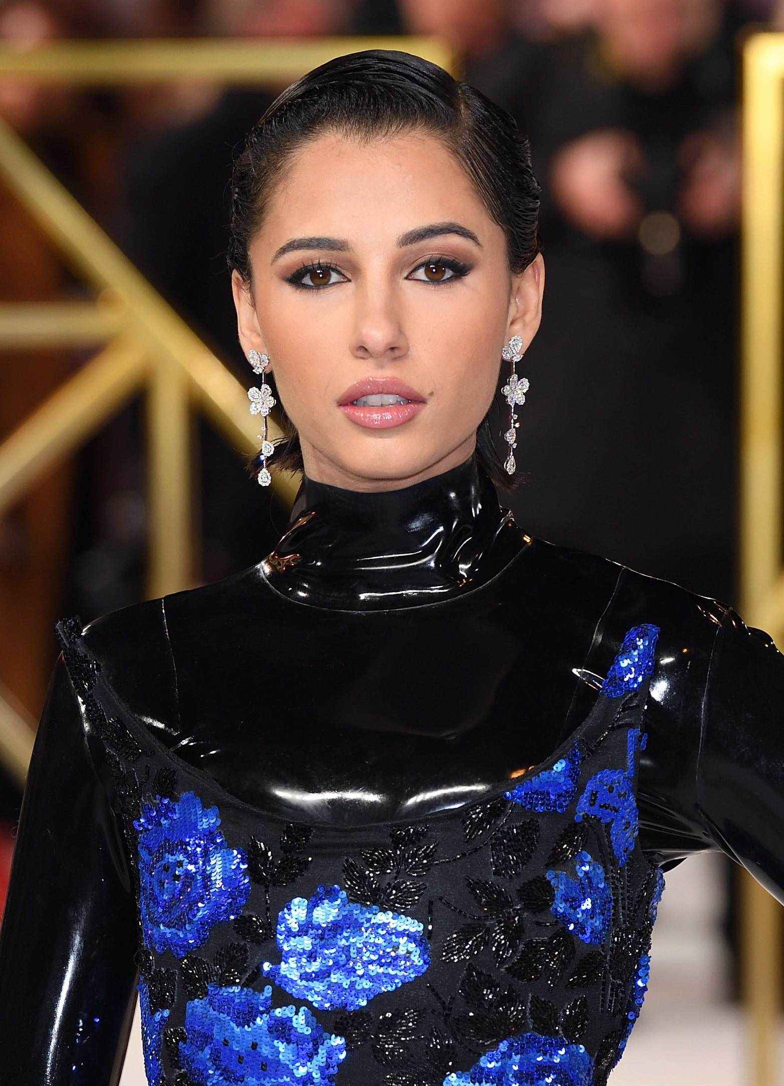 Naomi Scott looks into the camera at a Charlie's Angels event, wearing a latex black turtleneck and sequenced blue and black dress
