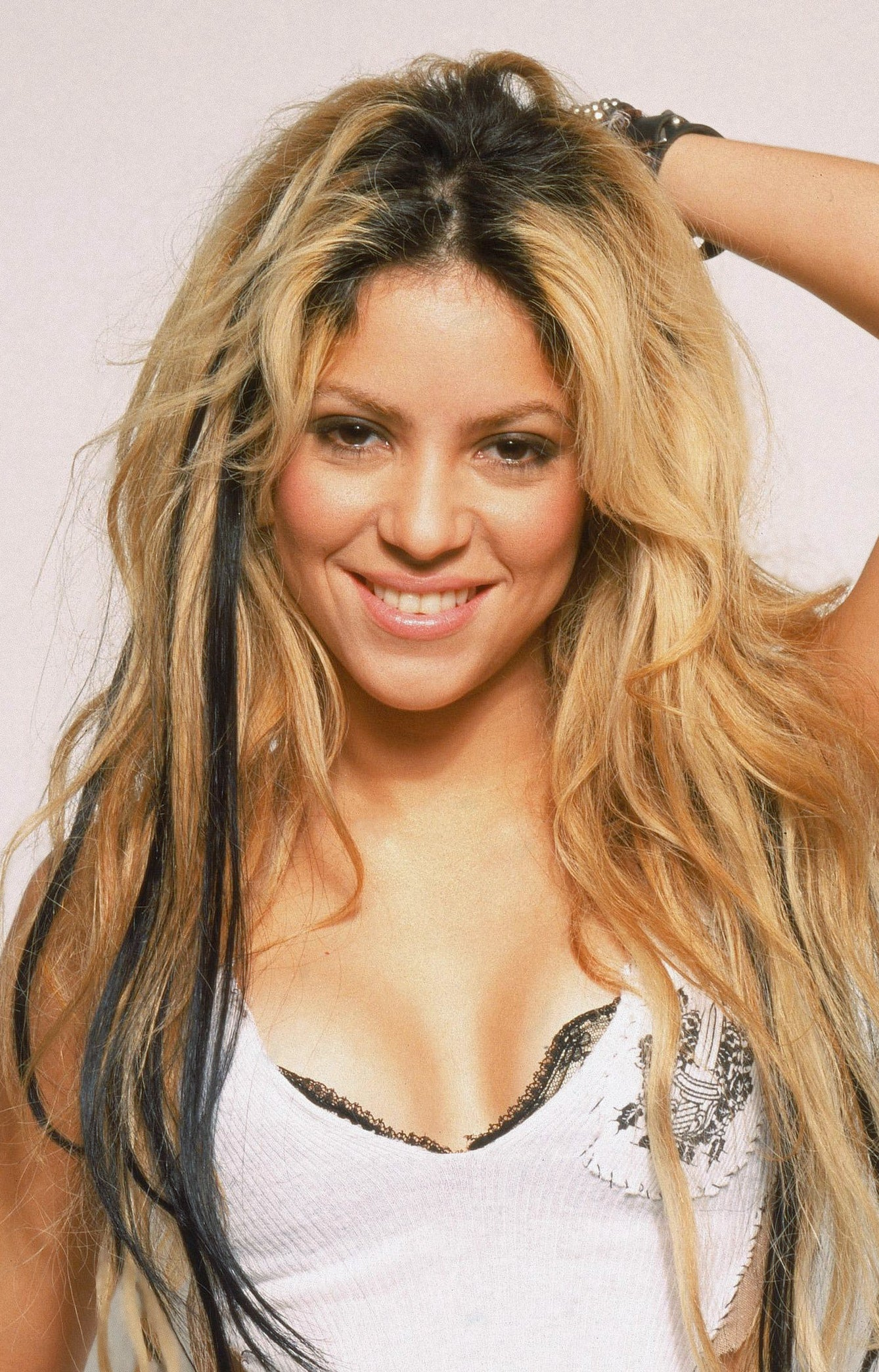 Shakira, with her black streaks in her blonde hair, smiling into the camera
