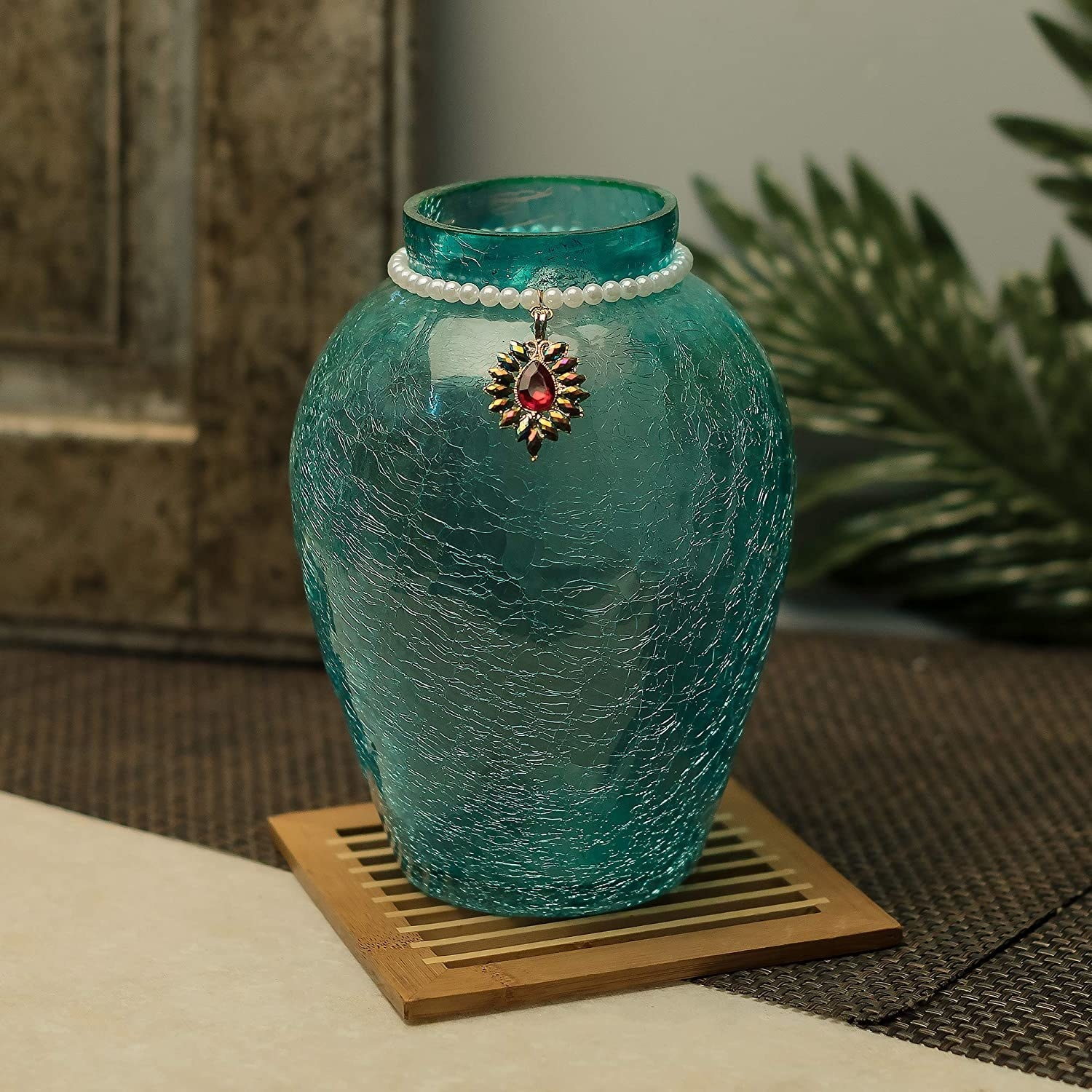 A turquoise vase with a necklace around the top