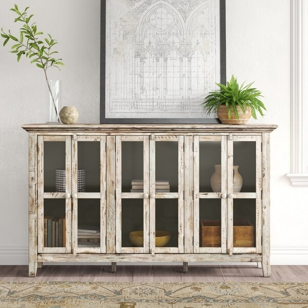 The sideboard in white distressed wood, which has three sets of glass-doored cabinets, and two interior shelves