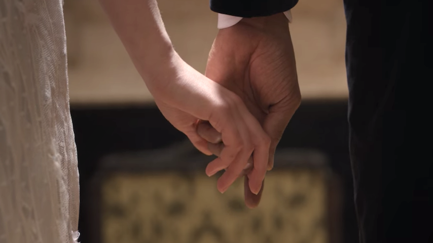 Simon and Daphne holding hands in front of a portrait