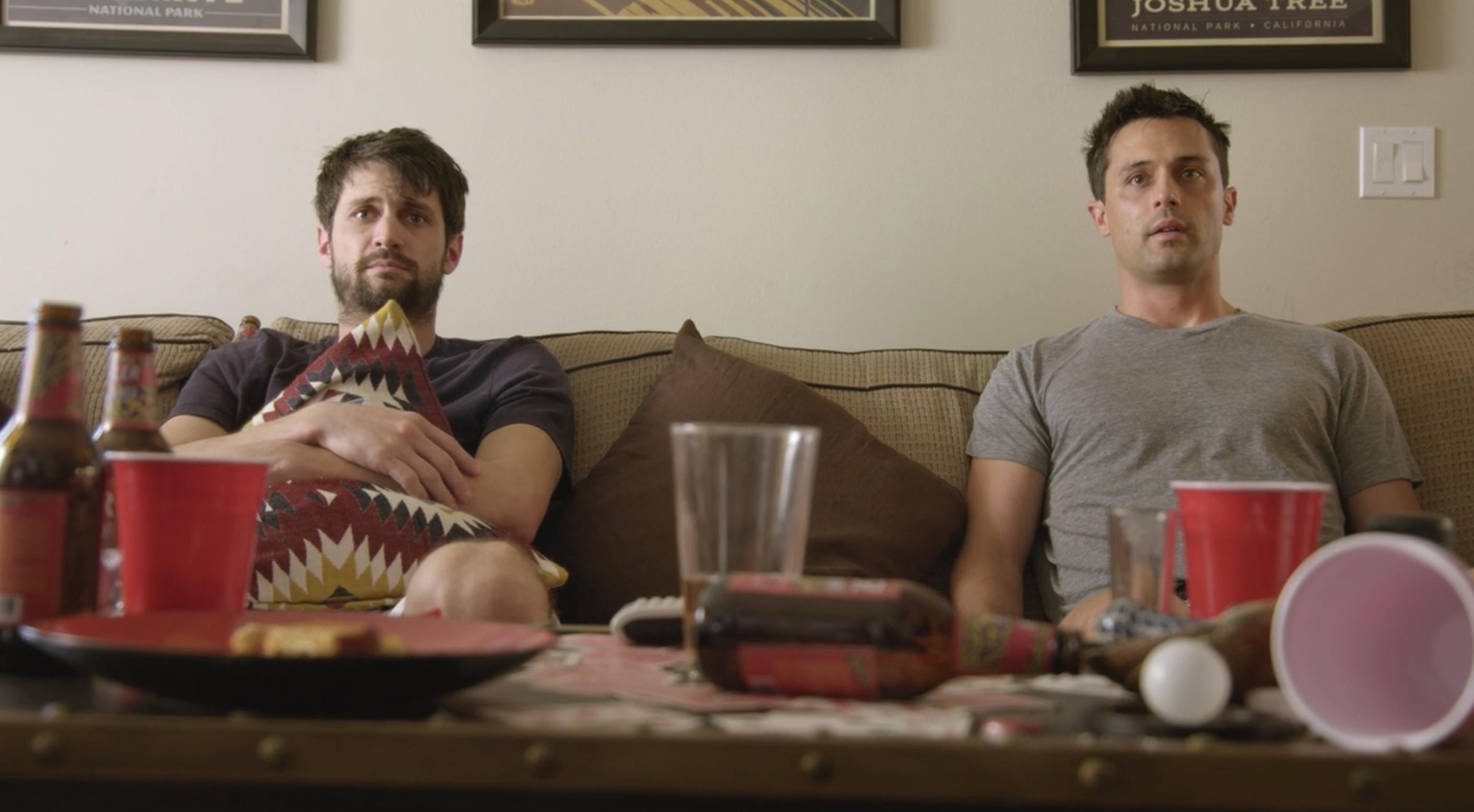 James Lafferty and Stephen Colletti sitting on a couch behind a table strewn with Solo cups and beer bottles