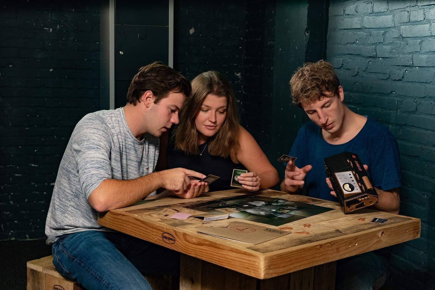 three people sitting around a table trying to solve the escape room puzzle