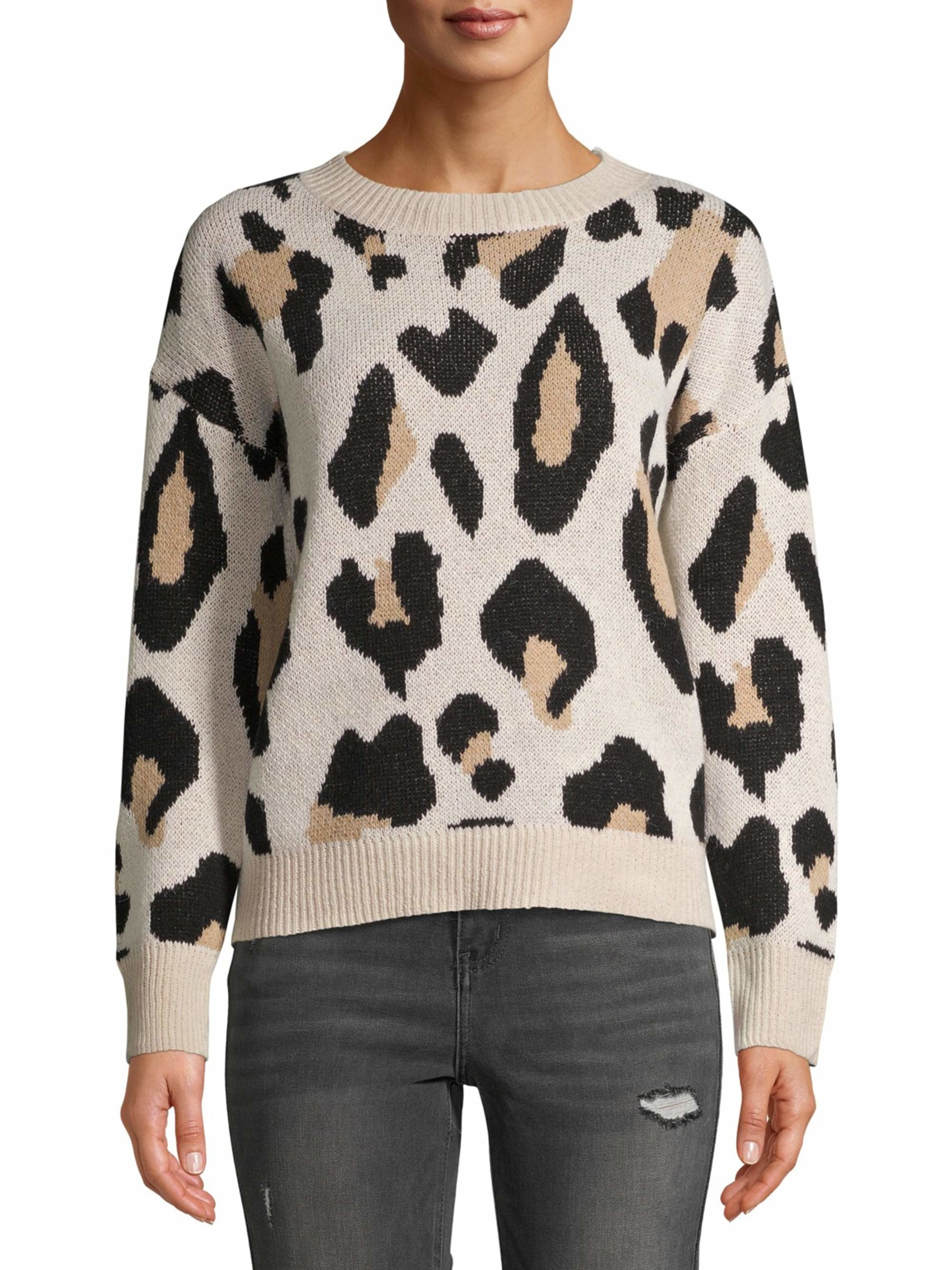 person wearing a leopard print sweater and black distressed jeans