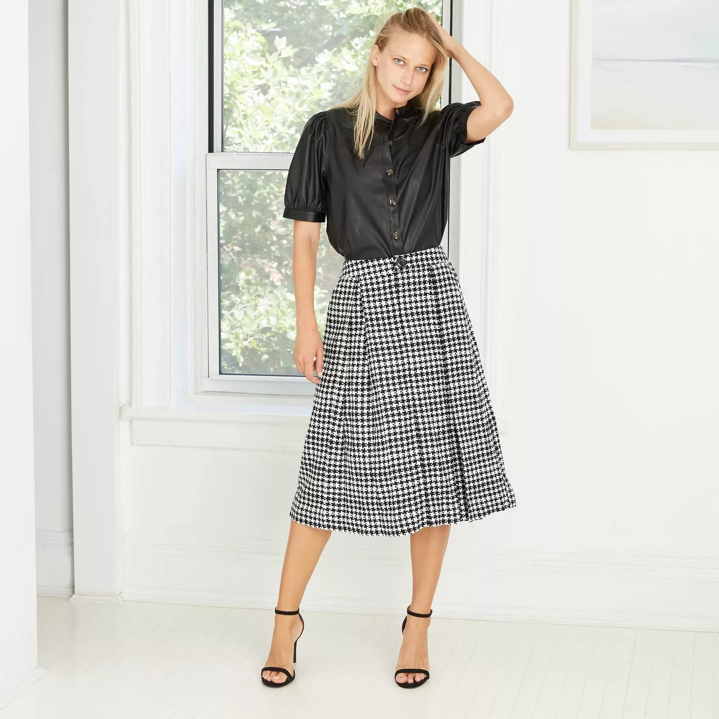 model wears button down leather shirt tucked into a plaid midi skirt