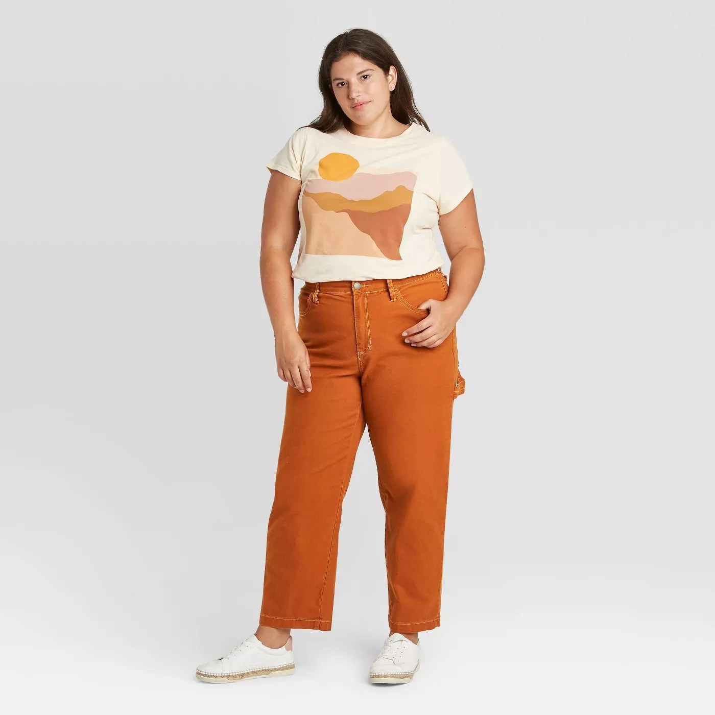 model wears vintage style orange pants with white sunset t shirt