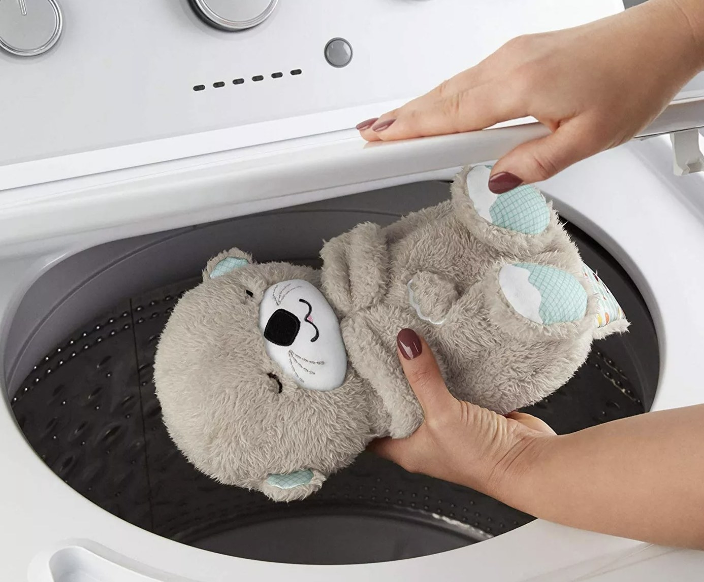 Person is holding otter plush over a washing machine