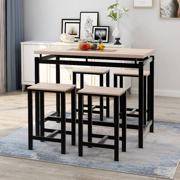 a pub table and four bar stools with wood tops and steel edges