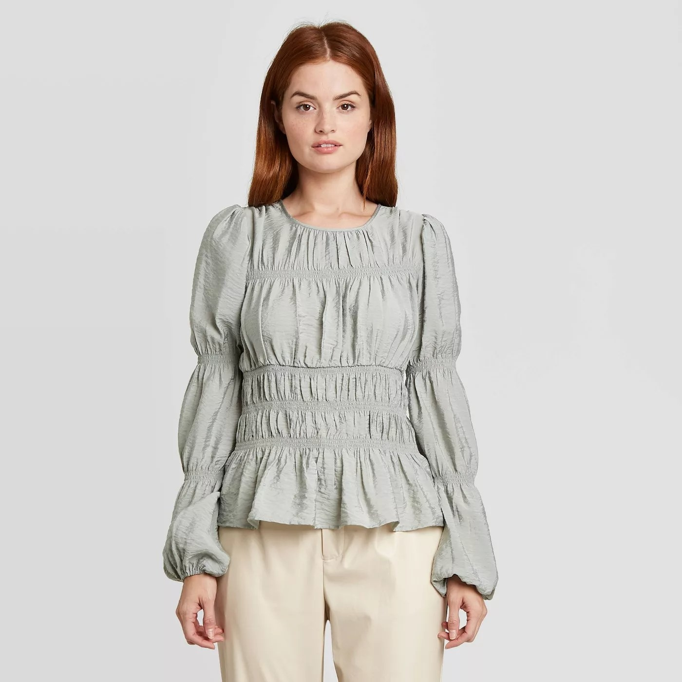 model wears cinched waist and tiered puff  sleeved muted green blouse