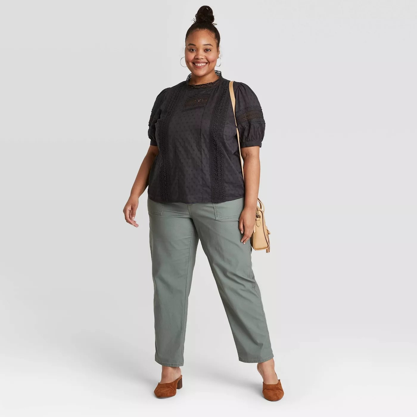 model wears black eyelet blouse with green khaki pants