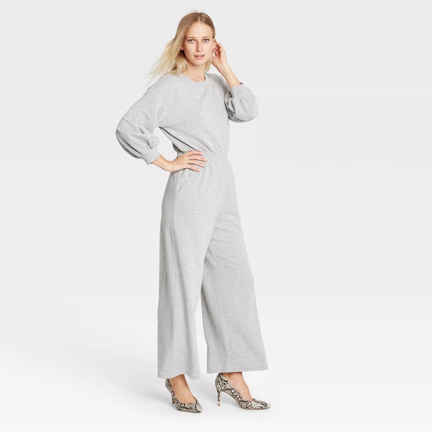 a model wears a grey long sleeve jumpsuit