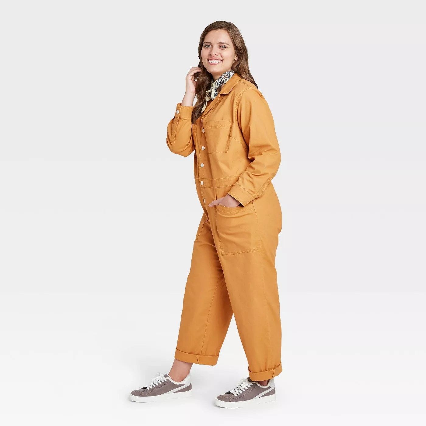 model wears mustard yellow coveralls with gray sneakers