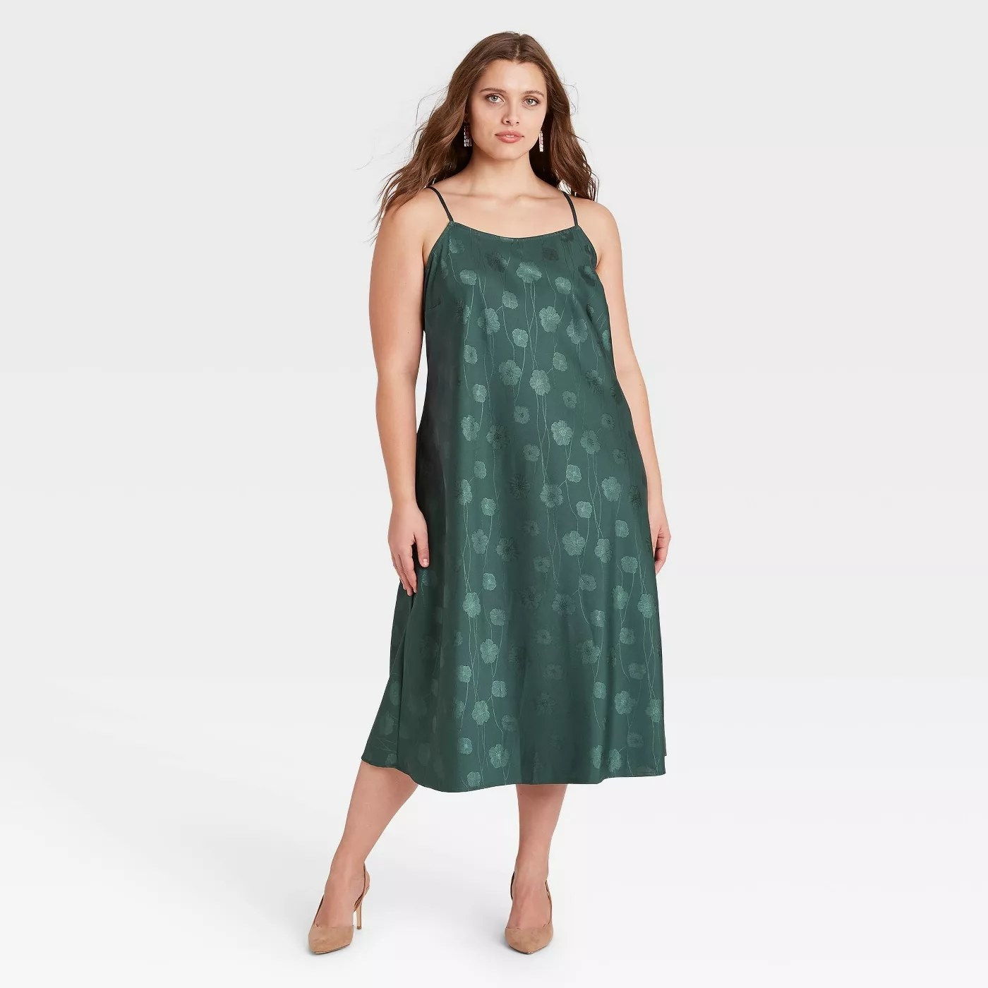 a model wears an emerald green slip dress