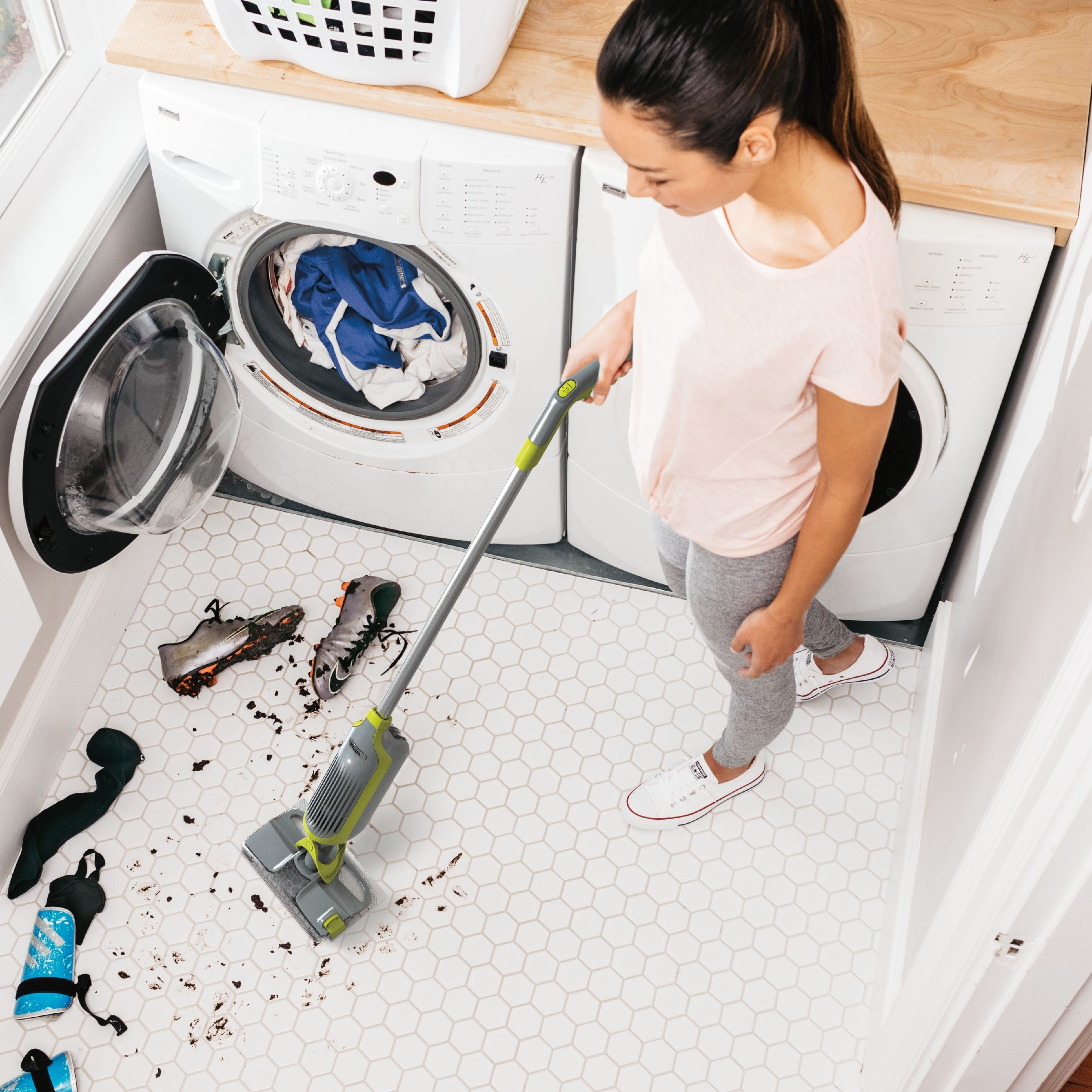 person using shark vacuum mop to clean up a dirty tile floor