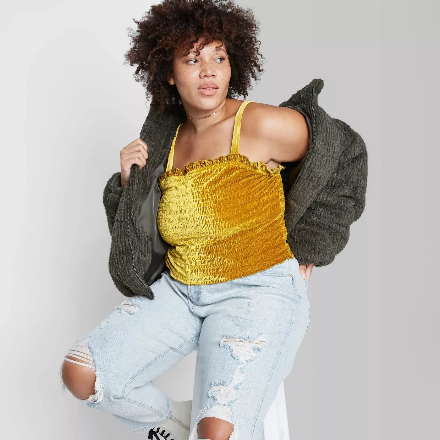 model wears smocked cropped gold velvety tank top with puffer jacket and ripped jeans