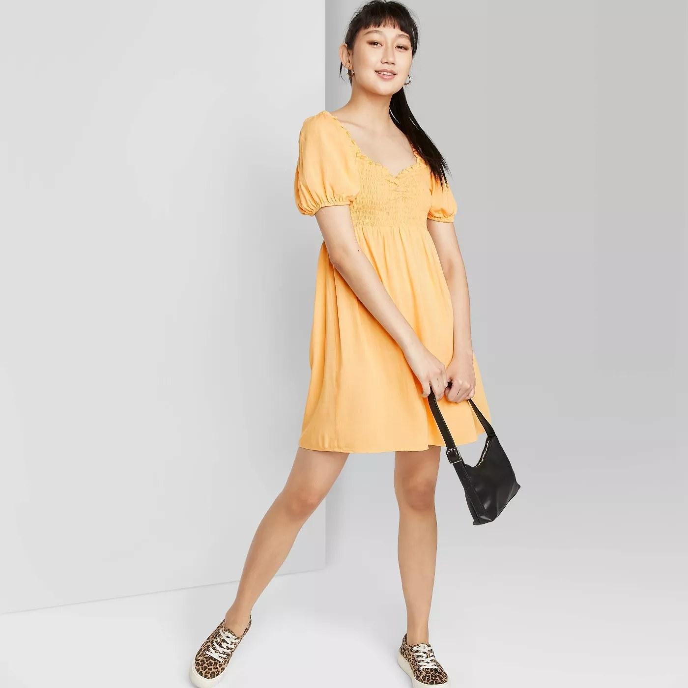 model wears yellow puff sleeved dress