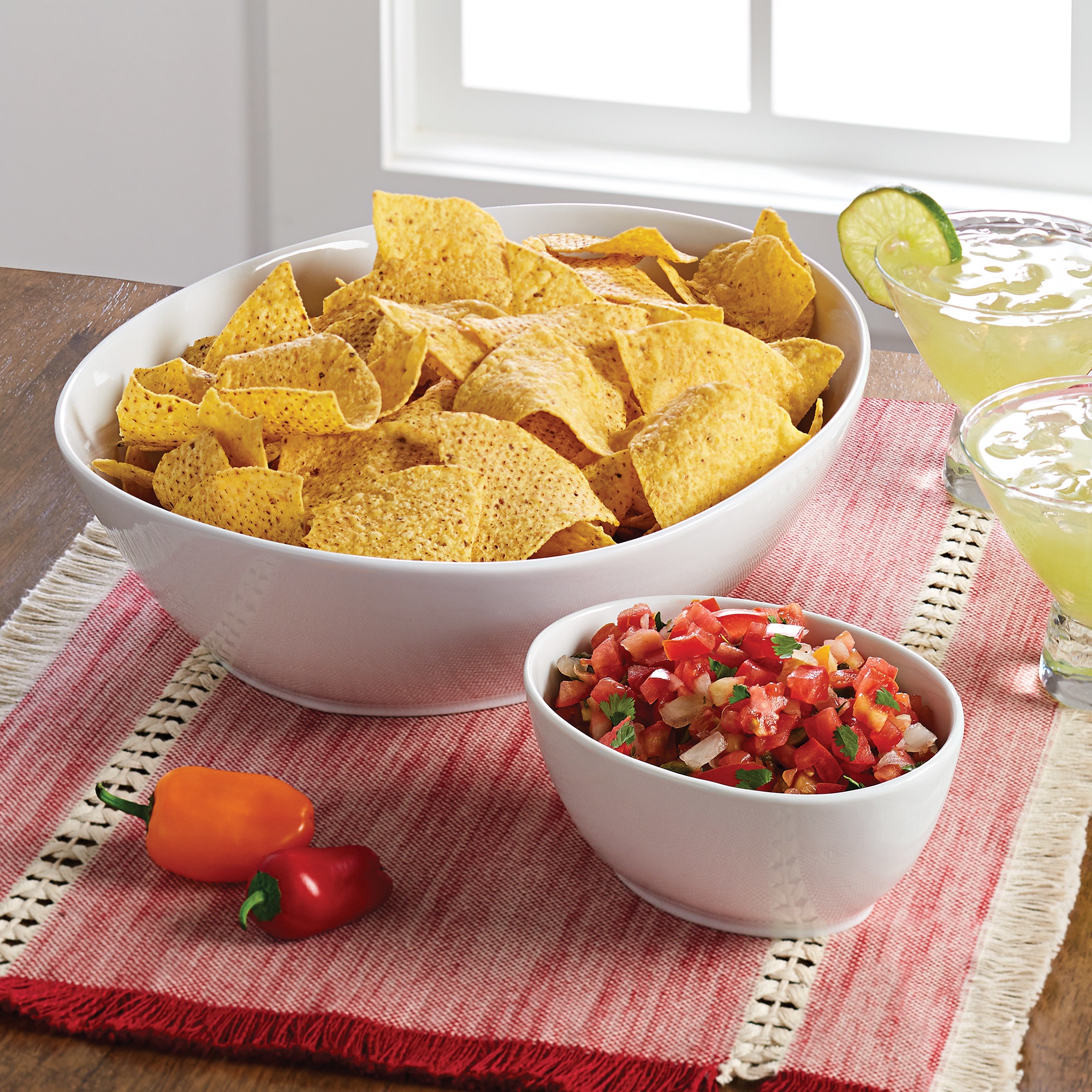 two porcelain bowls, one with tortilla chips and one with pico de gallo