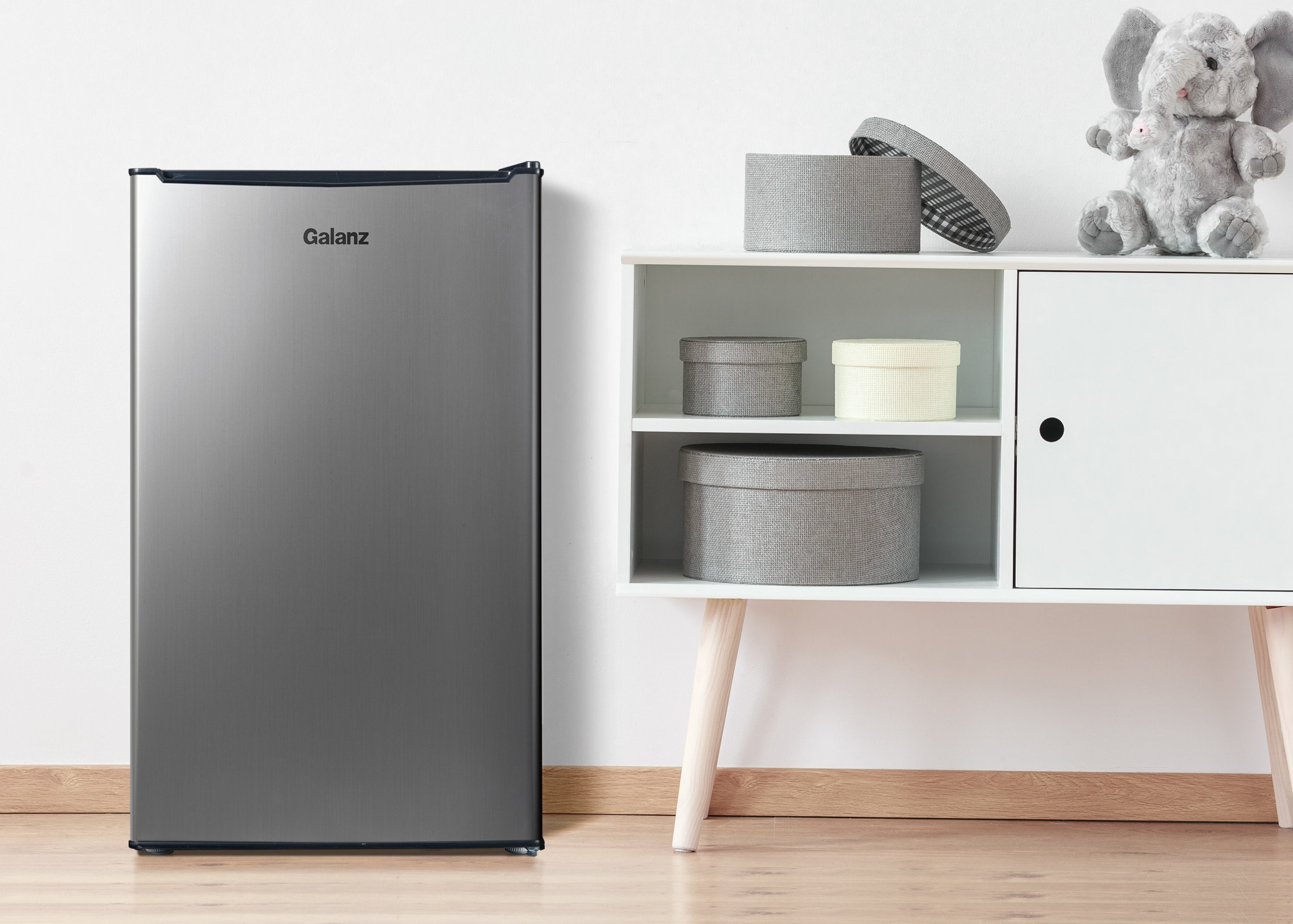 stainless steel galanz mini fridge next to a cabinet with baby materials