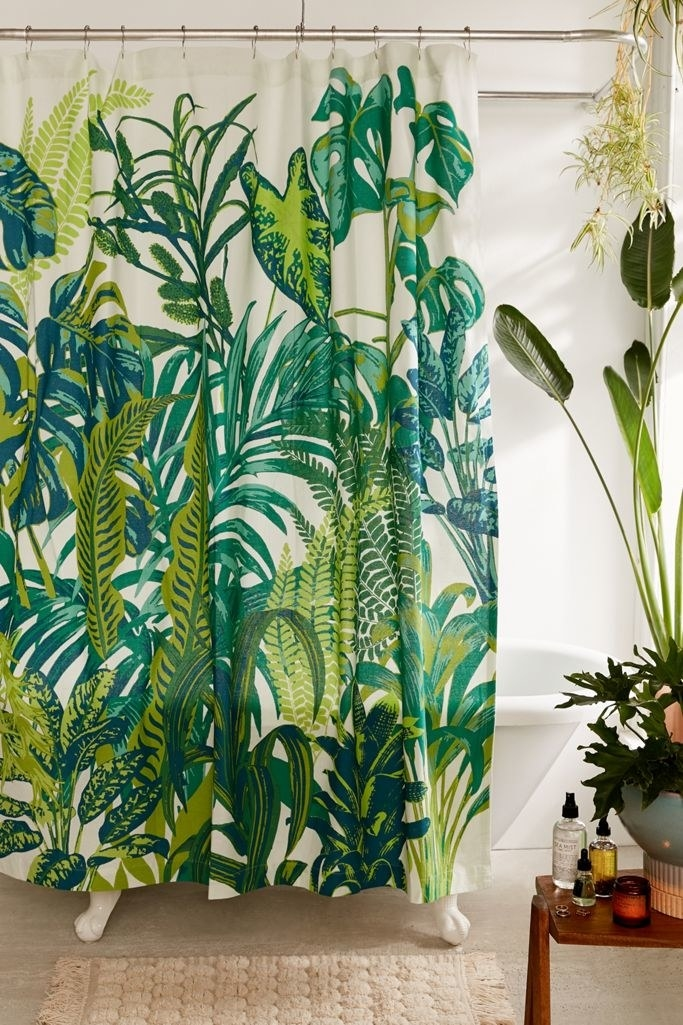 Green and white shower curtain with several leaves