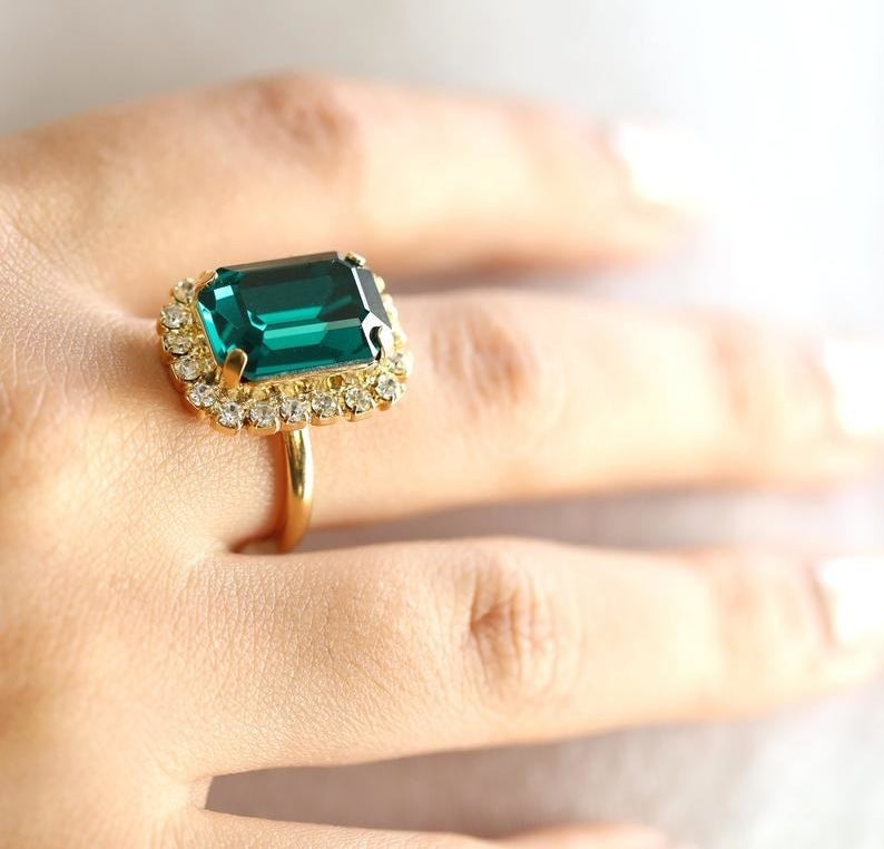 Hand wearing gold ring with small crystals and large emerald center stone