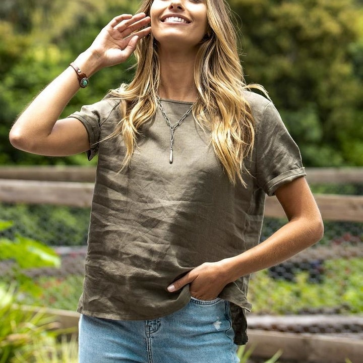 Front view of a different model wearing the olive linen shirt untucked