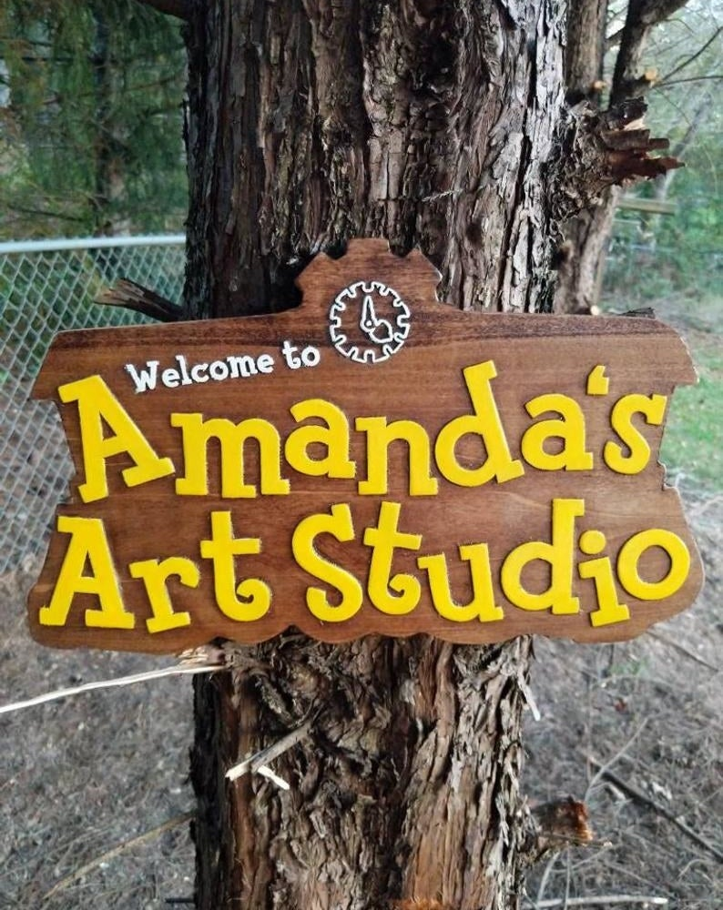 """A large wooden sign that looks just like the animal crossing logo but with the words """"Welcome to Amanda's Art Studio"""""""