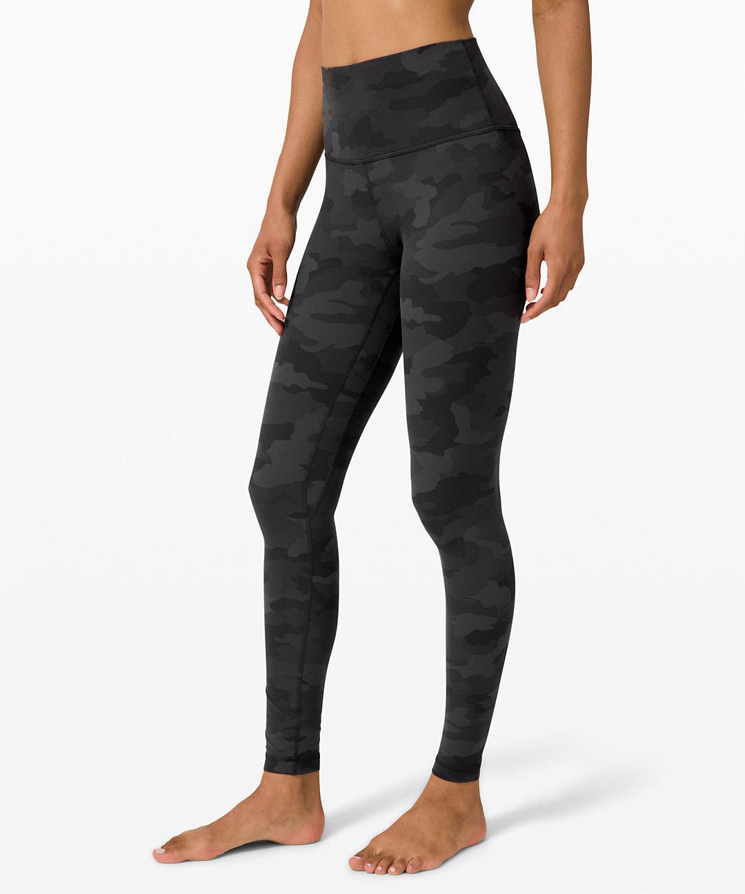 model wearing the full-length high-waisted leggings in black and dark grey camo