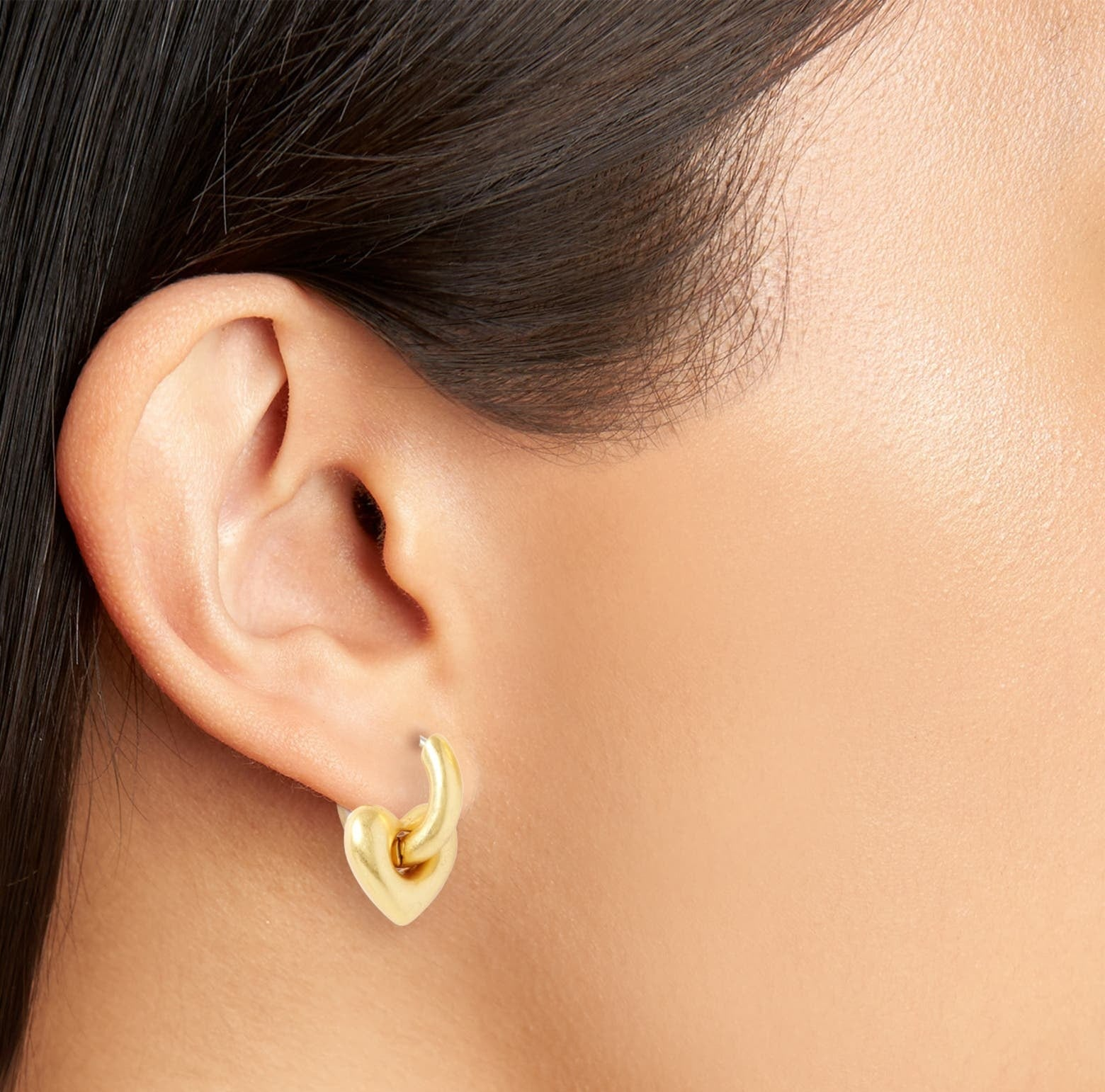 a thick, gold heart shape hoop inside of another gold hoop on an ear lobe.