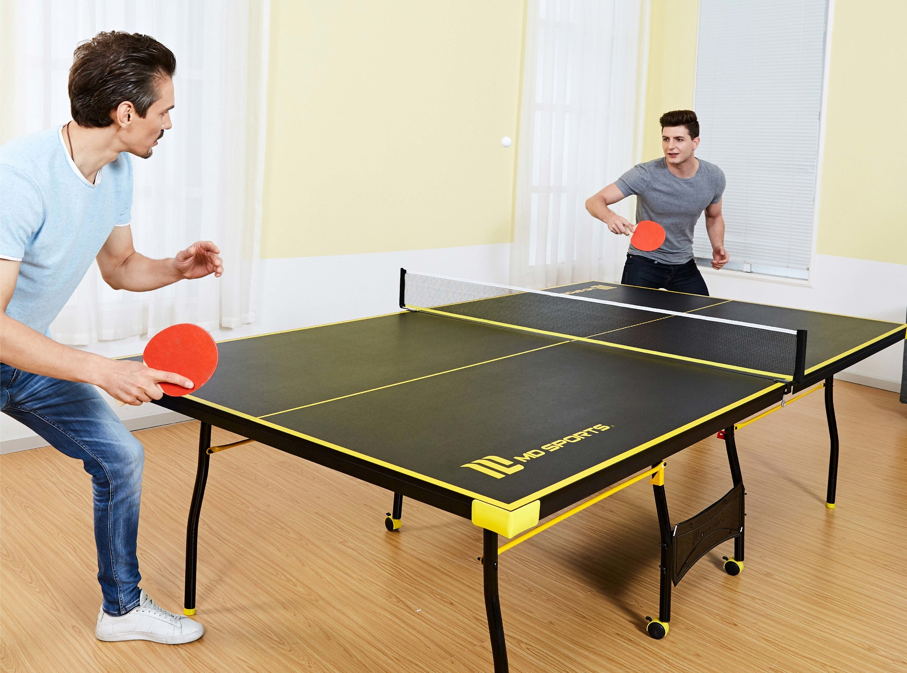 two people playing ping pong over a table tennis table