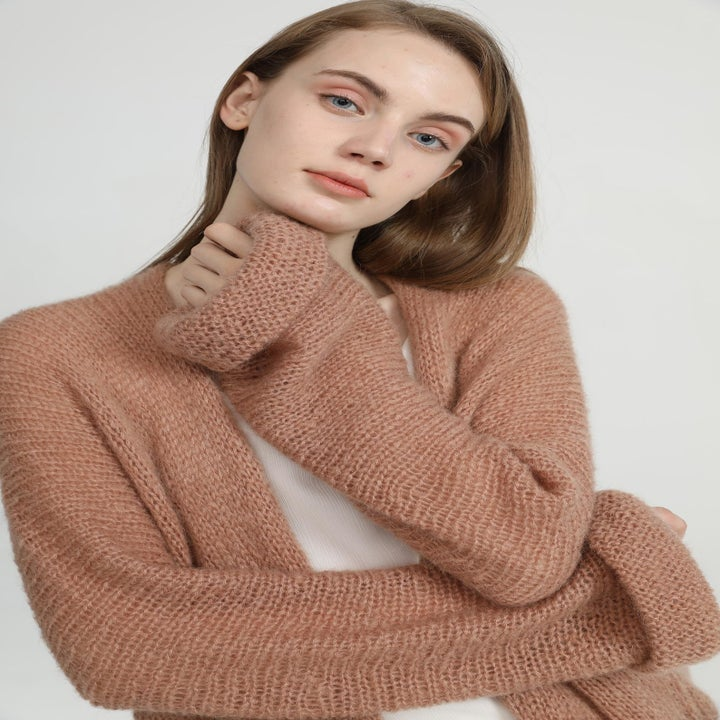 Zoomed in shot of a model wearing the cardigan which has cuffed sleeves