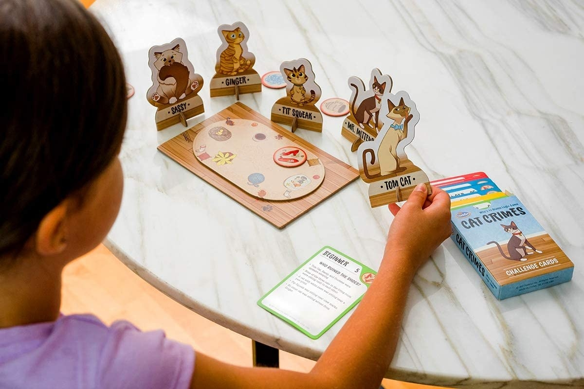 child with the game set up with standing cat cards holding one