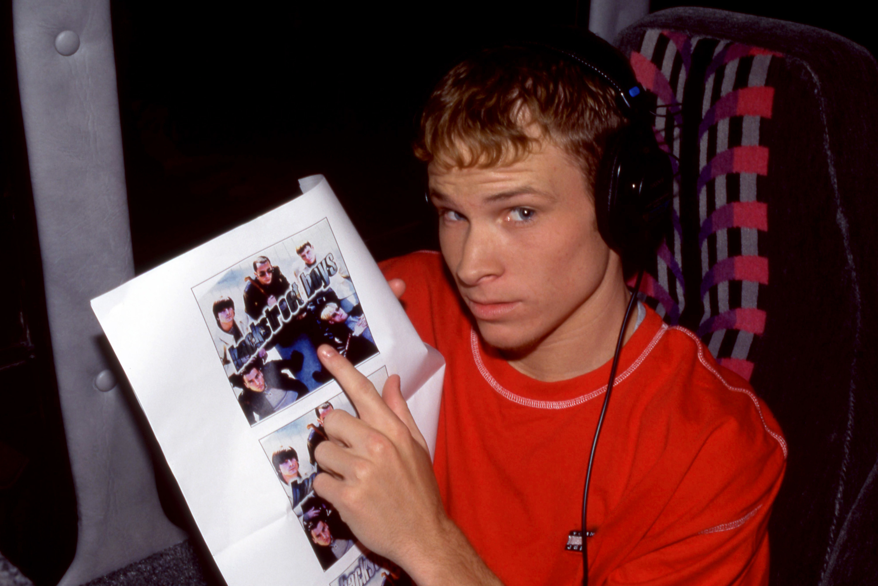 Brian pointing to a promotional photo of the BackStreet Boys