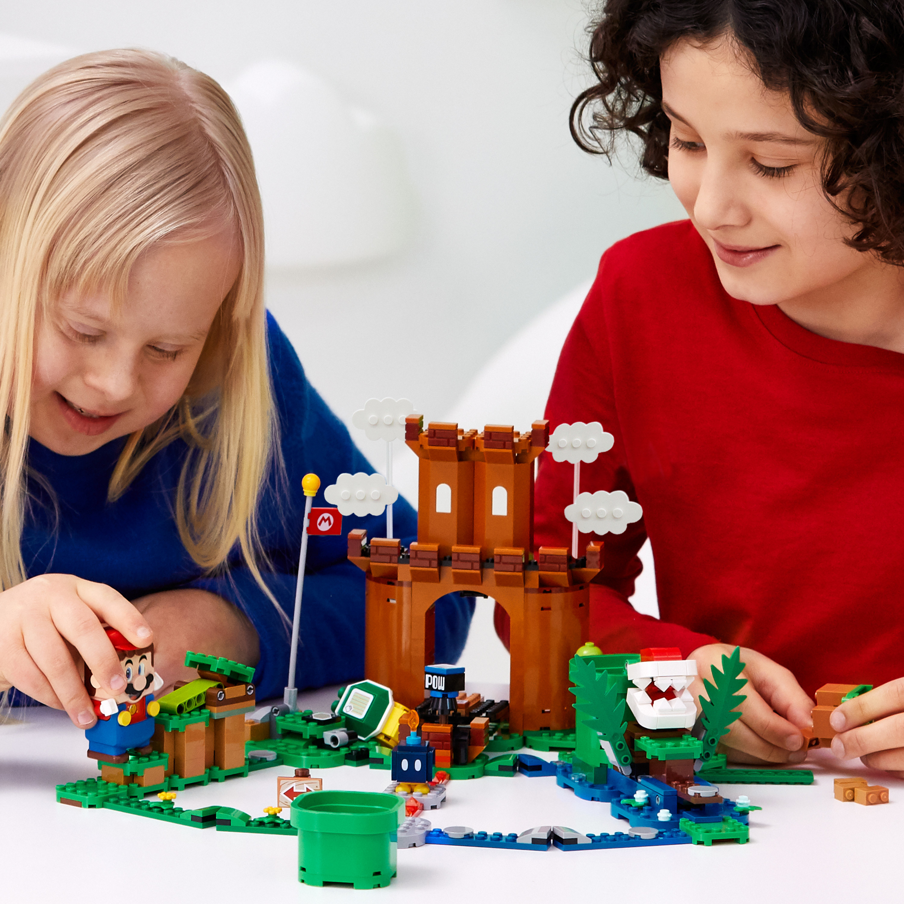 two children playing with a super mario building playset