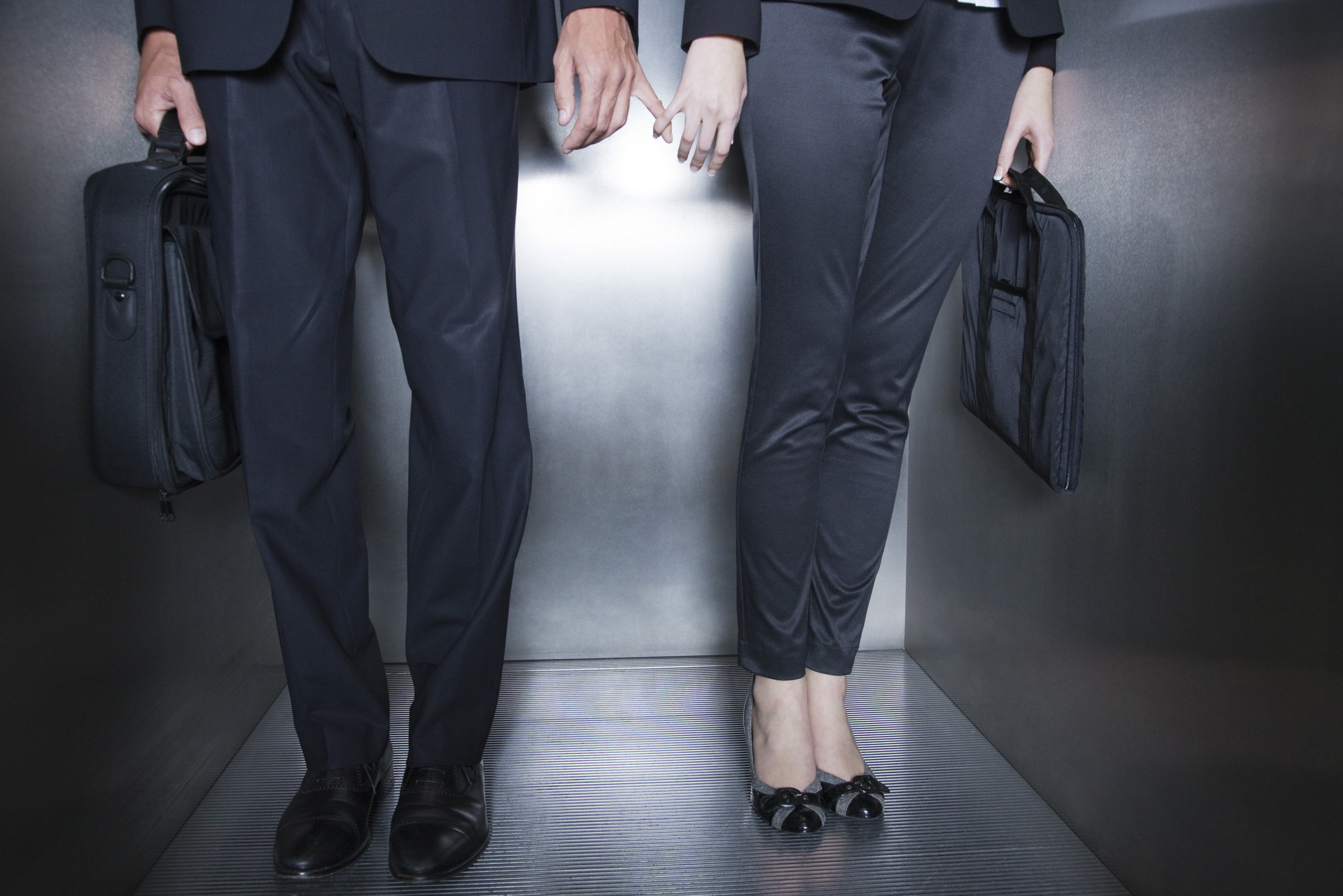Coworkers in an elevator holding pinkies