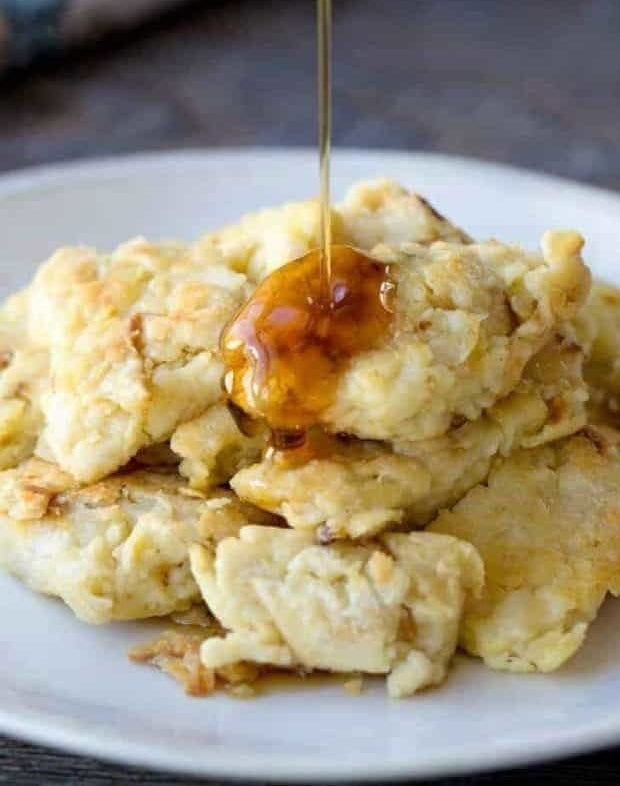 Matzo brei on a plate being drizzled with maple syrup.