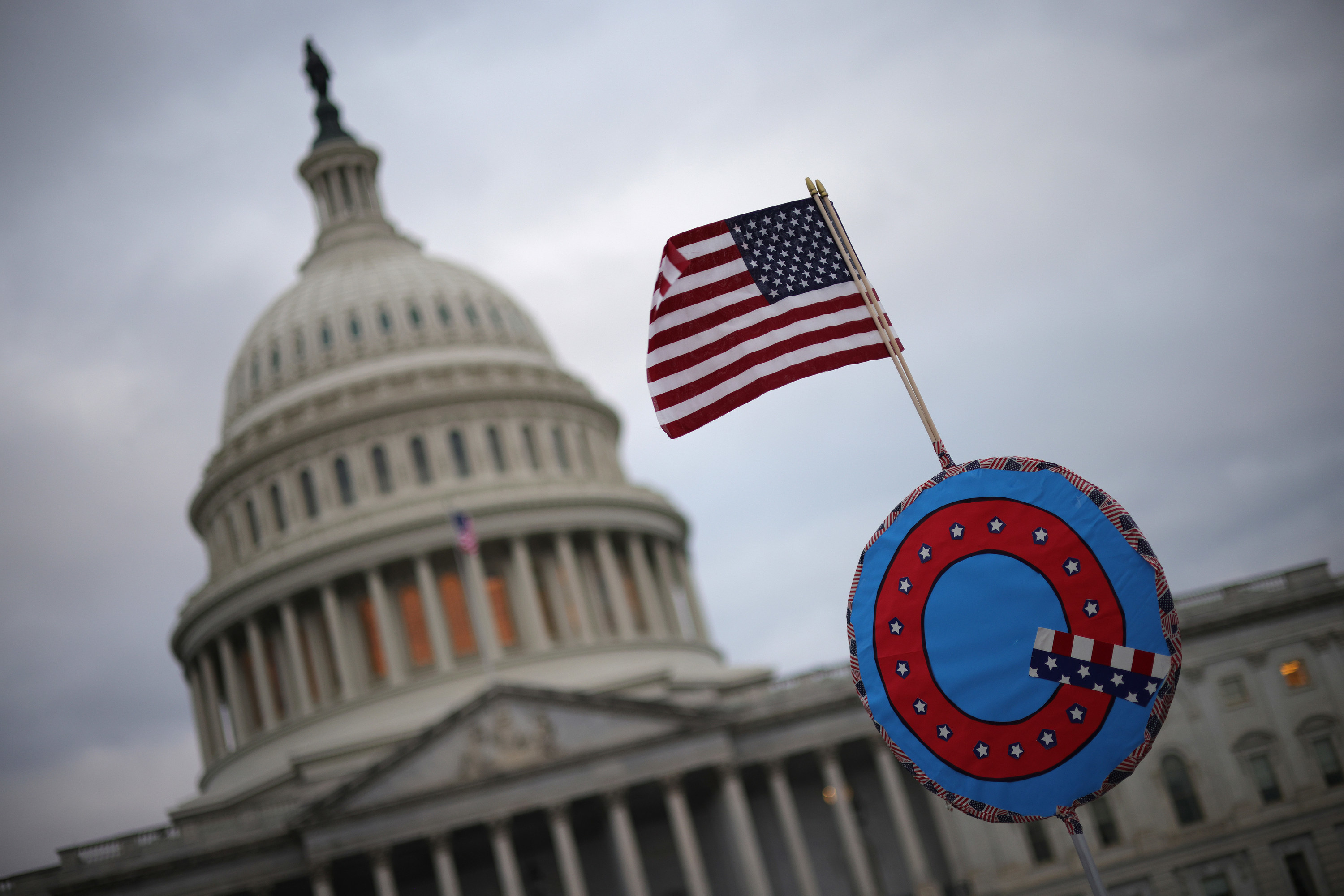"A mini US flag set atop a ""Q"" in front of the Capitol"