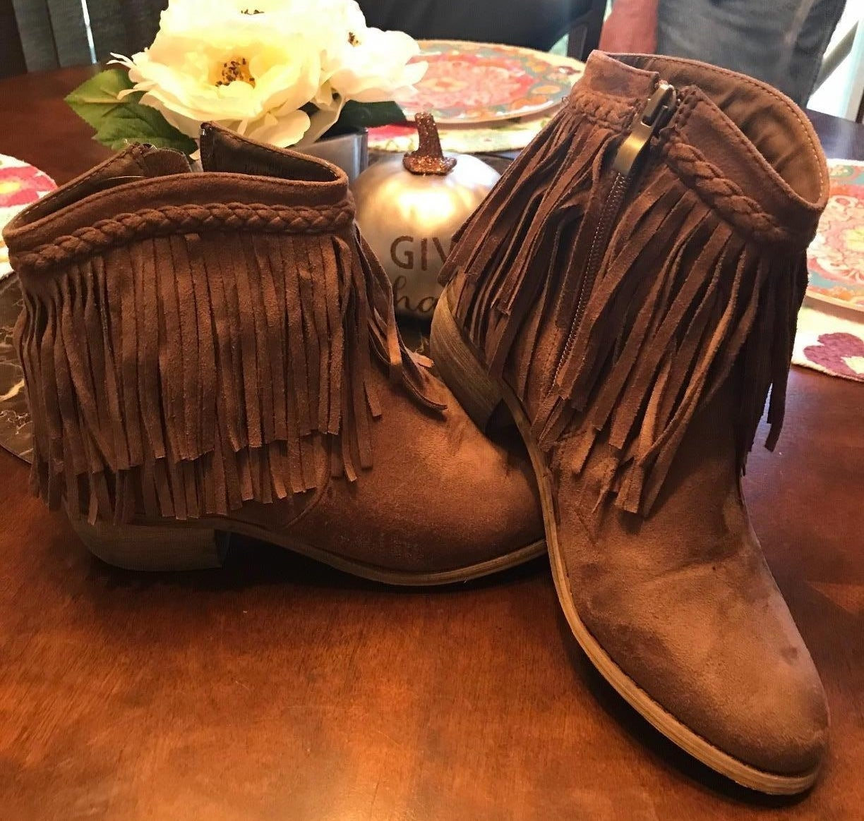 reviewer images of the booties with two layers of fringe around the ankle in brown